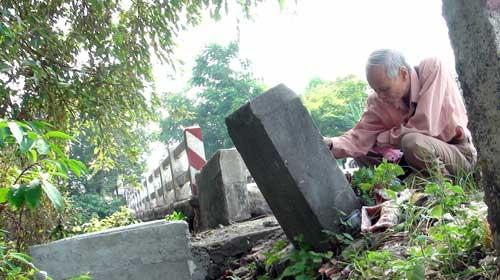 """Nhà sưu tập cổ vật Hồ Tấn Phan bên bia đá """"Lợi Tế kiều"""" ở đầu cầu Kim Long. Ảnh: Thái Lộc"""