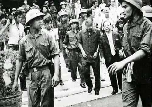 Phạm Xuân Thệ (phải, đại úy trung đoàn phó trung đoàn 66 sư đoàn 304) & Bàng Nguyên Thất (trái, binh nhất) dẫn giải Tổng thống Dương Văn Minh & Thủ tướng Vũ Văn Mẫu từ dinh Độc Lập sang Đài Phát thanh Sài Gòn trưa 30-4-1975. Ảnh này do ai chụp?